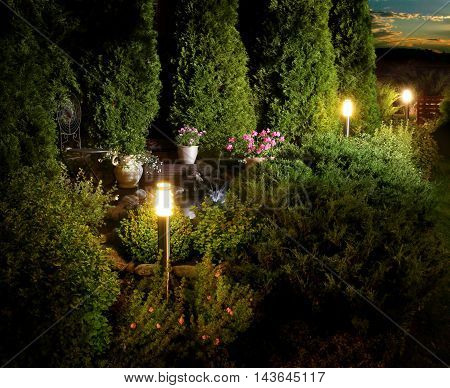 Illuminated home garden patio plants and fountain on evening dusk