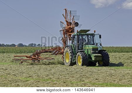 YSBRECHTUM, THE NETHERLANDS - AUGUST 22, 2016: A green tractor with a Kuhn rotary rake using one rotor for making small windrows for quicker drying of the hay.