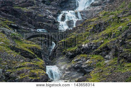 Norway Camper Van Trip. Trollstigen Bridge Stigfossen Falls and Serpentine Mountain Road in Rauma Municipality Norway. Motorhome on the Scenic Waterfall Bridge.