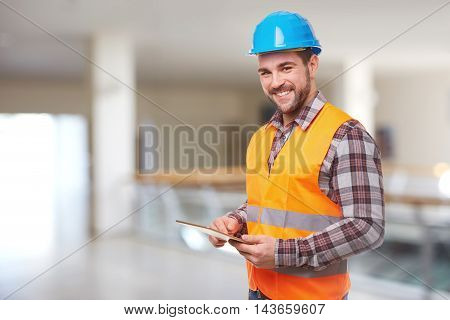 Manual Worker In Blue Helmet Using A Digital Tablet