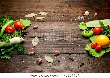 Fresh vegetables: tomatoes, pepper, leek, salad and potherbs on the dark wood table