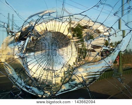 Street mirror broken by vandals in which is reflected the city. Horizontal.