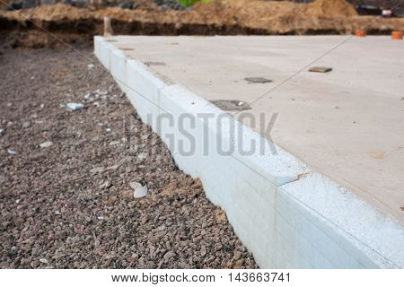 Closeup of fundation of new house under construction with insulation layer - styrofoam boards