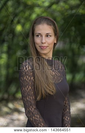 Portrait of pretty cute beautiful woman in park. Stock photo.