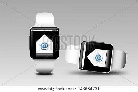 modern technology, responsive design and communication concept - smart watches with e-mail letter icon on screen over gray background