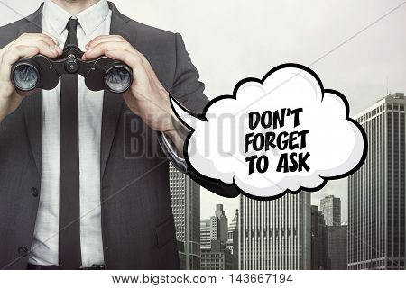Dont forget to ask text on speech bubble with businessman holding binoculars on city background
