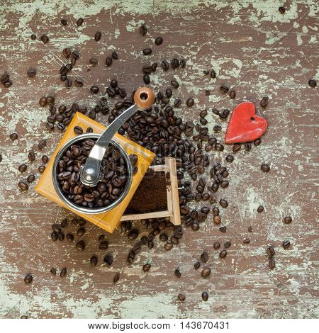 Old coffee grinder and red colored heart shape