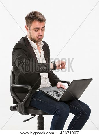 a hurry, bewilderment, chair, clerk, confusion, deadline, delay, despair, emotion, fear, haste, holding, laptop, limit, looking at his watch, looks surprised, male, man, manager, office, office worker, panic, rush, shock, sitting, student, studio, thinkin