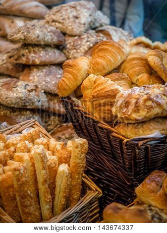 Close up of freshly baked buns, croissants and breadsticks on market stall in Borough market in London