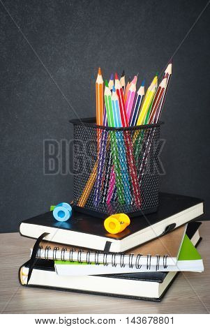School supplies on classroom table in front of blackboard. View with copy space
