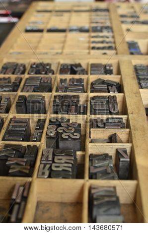 Side View Of Metallic Etterpress Letters In A Wooden Box