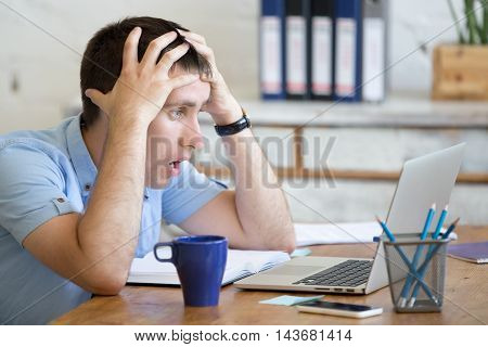Young Shocked Office Man Looking At Laptop Computer