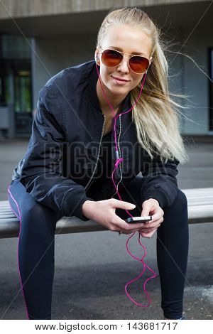 Beautiful and smiling woman with sunglasses sits on a bench in the city wearing a bomber jacket and sportswear. Listens to music and using smart phone.