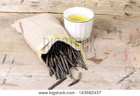 Wellness Tea drink, Bitter Twisted Leaves of Ilex Kudingcha. Green tea Kuding in a sackcloth