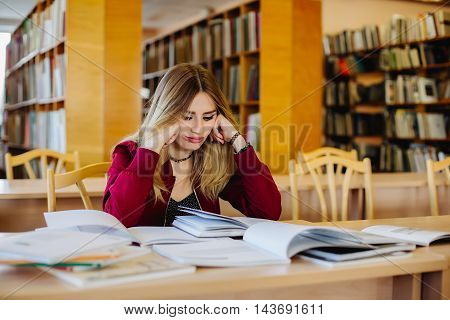 Fatigue concept. Bored and tired attractive female student sitting at desk in old university library preparing for exam and reading books. Education process.