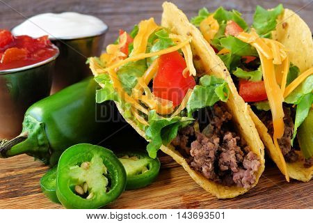 Hard Shelled Tacos With Ground Beef, Lettuce, Tomatoes And Cheese Close Up, On Rustic Wood