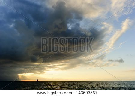 Journey is a small boat sailing towards the light of spiritual faith freedom and hope as an approaching surreal storm looms overhead.