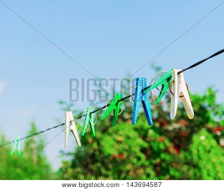 Plastic clothespins laundry hook colorful rope.Village plastic pegs. Two white clothes pins one blue clothespin rope on focus four green clothespins. Summer rural landscape.