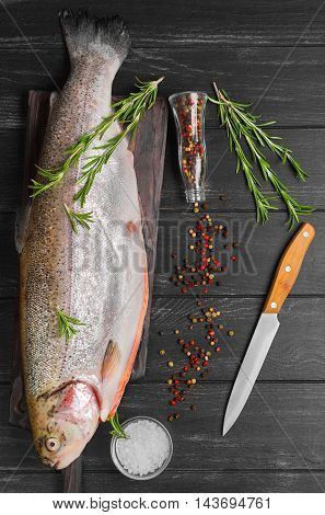 Cutting gutted red fish trout sweetfish on board spices trout rosemary different kinds of peppers salt dark black wood background rustic style top view
