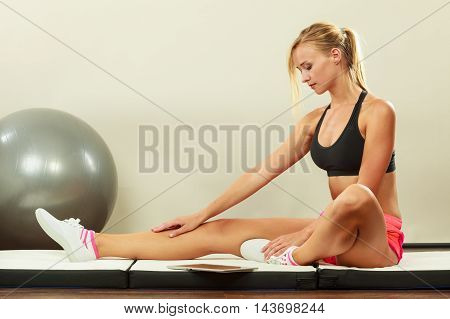 Fitness woman blonde fit girl sitting on floor and looking into tablet pc