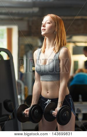Concept: sport, healthy lifestyle. Young strong girl do exercises with dumbbells