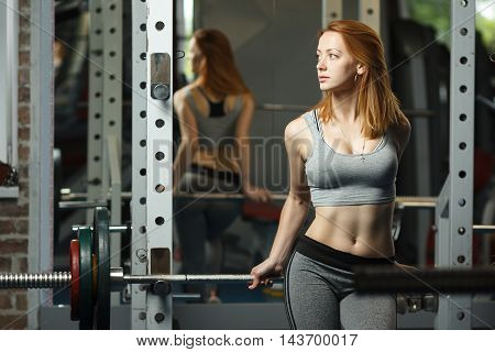 Concept: sport, healthy lifestyle. Young strong girl take breather in gym
