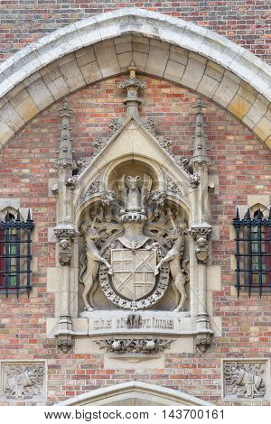 Brugge Belgium - August 10 2016: Elaborate mural of Coat of Arms at the gate to Gruuthuse Mansion now museum. Beige stone against bricks.