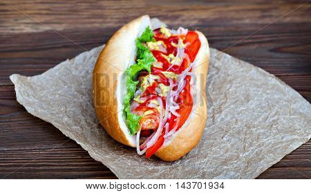 Big tasty hot dog with sauce and vegetables in parchment on the wooden background. hotdog gourmet.