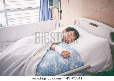 Asian Boy Lying On Sickbed With Saline Intravenous (iv). Health Care And People Concept. Vintage Ton