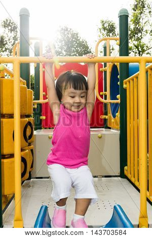 Asian Little Chinese Girl Hanging On Horizontal Monkey Bar