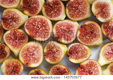 Background filled with fresh sliced figs. Close-up
