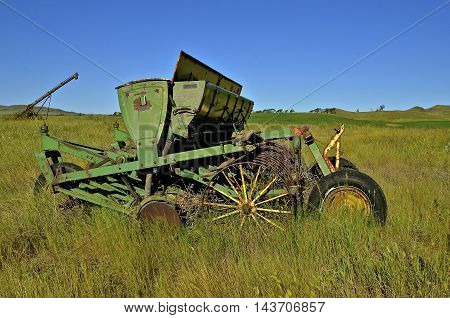 An old grain seeder with wide open seed boxes is left neglect4ed in a grassy field.