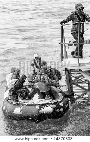 SOUTH GEORGIA, GREAT BRITAIN - NOV 9, 2012: Unidentified group of people in a water proof suit in a rubber boat with a motor in the Atlantic Ocean. Atlantic Ocean is the world's second largest ocean
