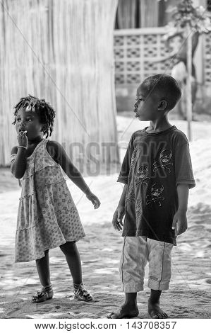 KARA, TOGO - MAR 9, 2013: Unidentified Togolese boy and girl playing in the street. Children in Togo suffer of poverty due to the unstable econimic situation