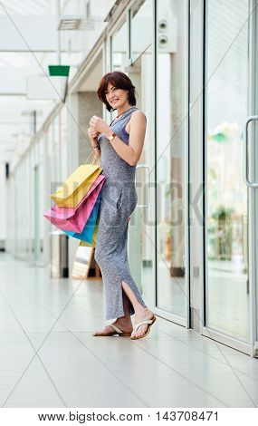 Beautiful, happy and fashionable woman with shopping bags at the mall