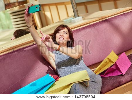 mature woman taking a selfie with their cell phone at the mall with shopping bags