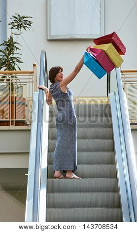 way to the next store. Rear view of beautiful young woman with shopping bags on mall escalator