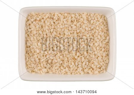 White sesame seeds in a ceramic bowl isolated on white background.