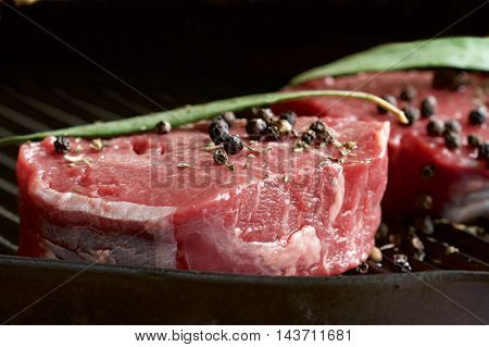 Raw beef eye fillet steak and peppercorns.