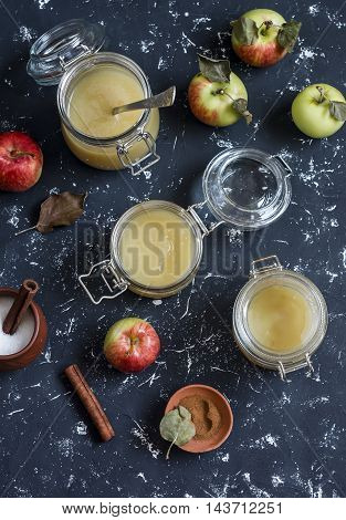 Homemade apple sauce in glass jars on dark background. Top view. Delicious seasoning for meat