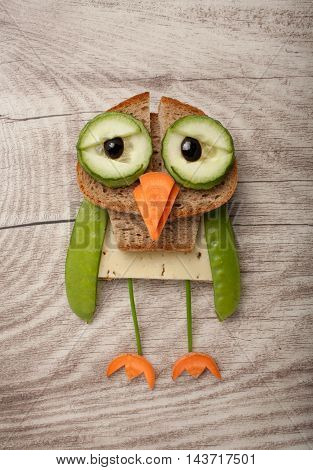Owl made of bread and vegetables on wooden background