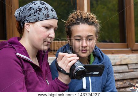 Two women young and mature holding video camera and showing footage sporty casual travel clothing wooden hut on background