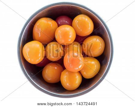 Bright, shiny orange pickled, salted tomatoes in a metal bowl with reflection on the sides macro isolated on white background