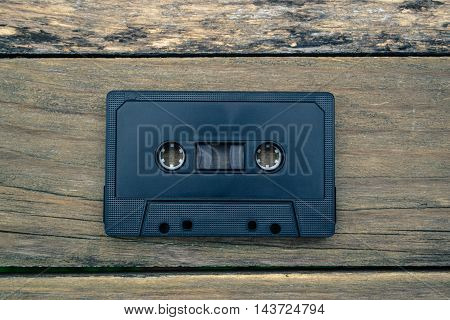 Vinyl records and cassettes on wooden background