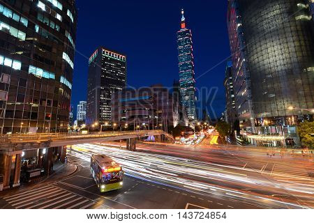 TAIPEI, TAIWAN - AUGUST 15, 2016 - A public city bus makes a right turn in busy traffic at an intersection near the 101 building in Taipei, Taiwan