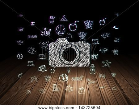 Tourism concept: Glowing Photo Camera icon in grunge dark room with Wooden Floor, black background with  Hand Drawn Vacation Icons