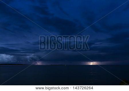 Thunderstorm at sea. Summer night, lights from an inlet and lightning flash from a thunderstorm.