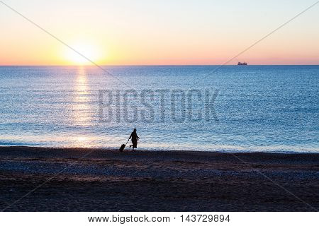 Exotic Vacation Silhouette of Female pulling Travel Suitcase along Ocean Beach Luminous Sunrise on Background