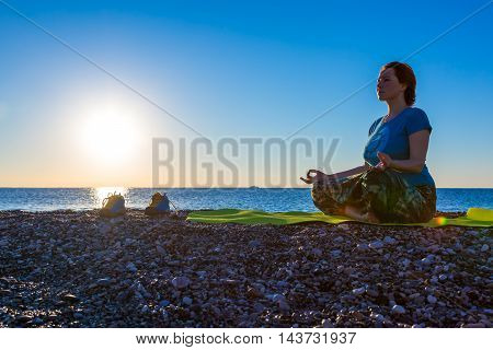 Young Woman meditating on rocky Ocean Beach sitting on green Yoga Mat sporty Shoes staying Sunrise with reflections Sea Surf blue Sky large copy space