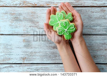 Woman holding decorative cookies. Saint Patrics Day concept